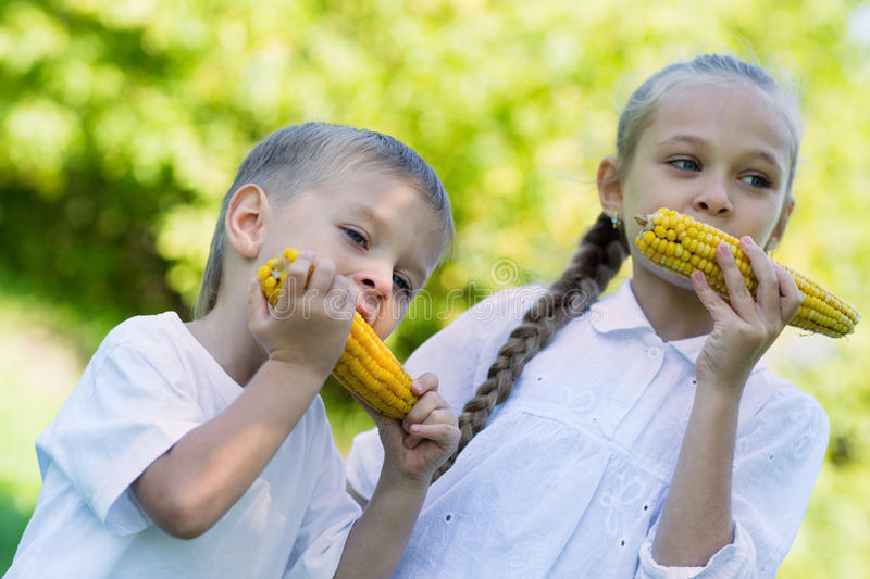 Boy and girl eating corn outdoors stock photo