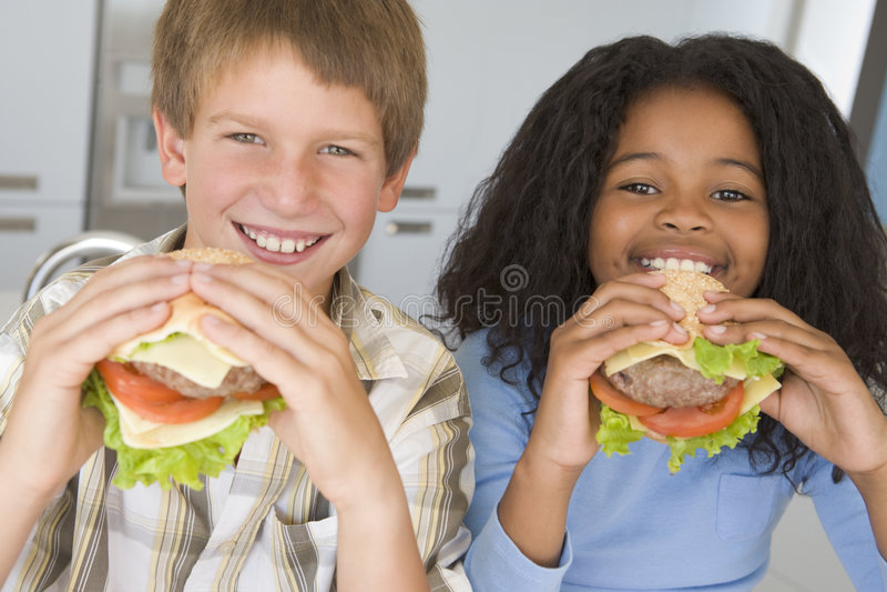 Boy and girl eating healthy burgers stock photos