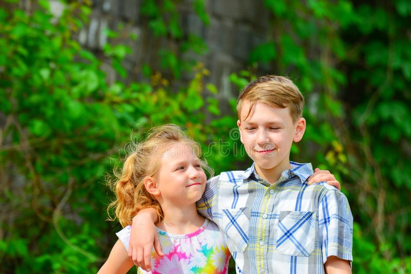 A boy and a girl are embraced in a park on the street and my sister is looking at her brother from below.  royalty free stock image