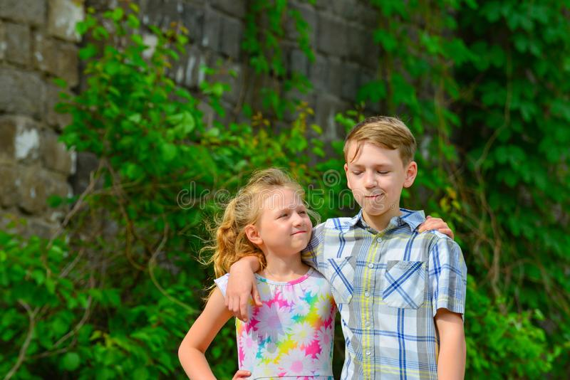 A boy and a girl are embraced in a park on the street and my sister is looking at her brother from below.  royalty free stock photos