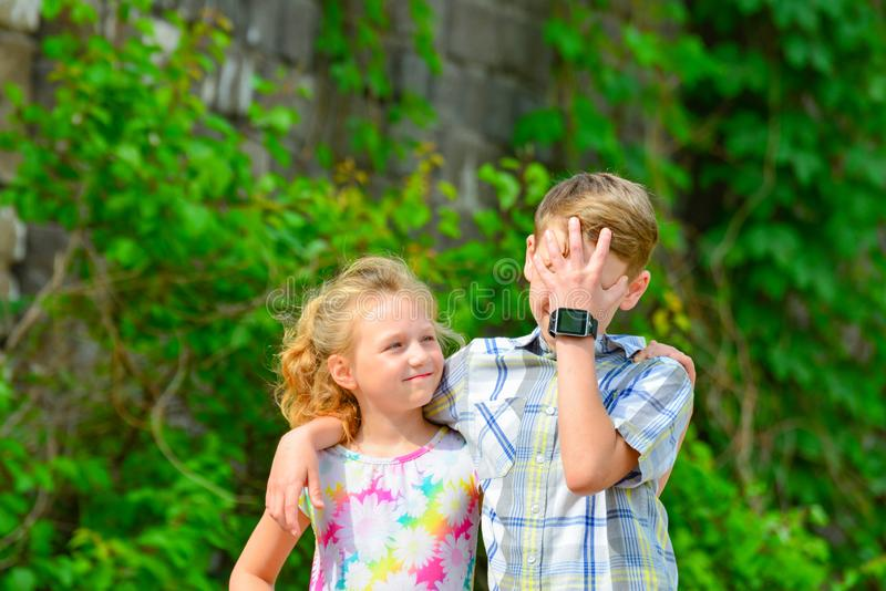 A boy and a girl are embraced in a park on the street and my sister is looking at her brother from below.  stock image