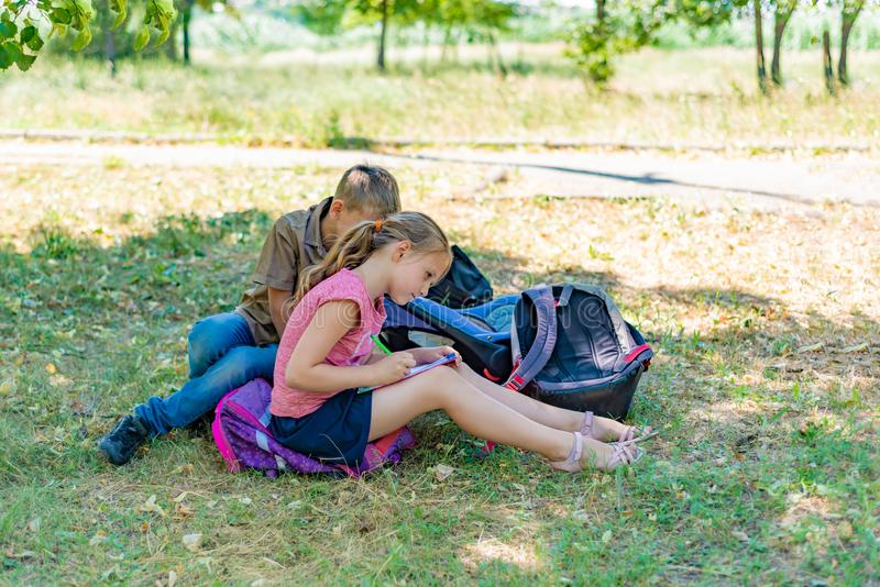 A boy and a girl are engaged in education and doing lessons in nature, preparing for entrance and final exams stock image