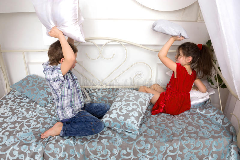 Boy and girl fighting pillows and playing on the bed. stock photo