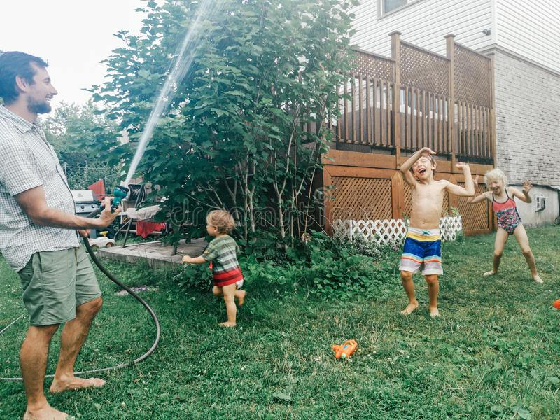 Boy girl friends siblings splashing playing under water on backyard on hot summer day stock images