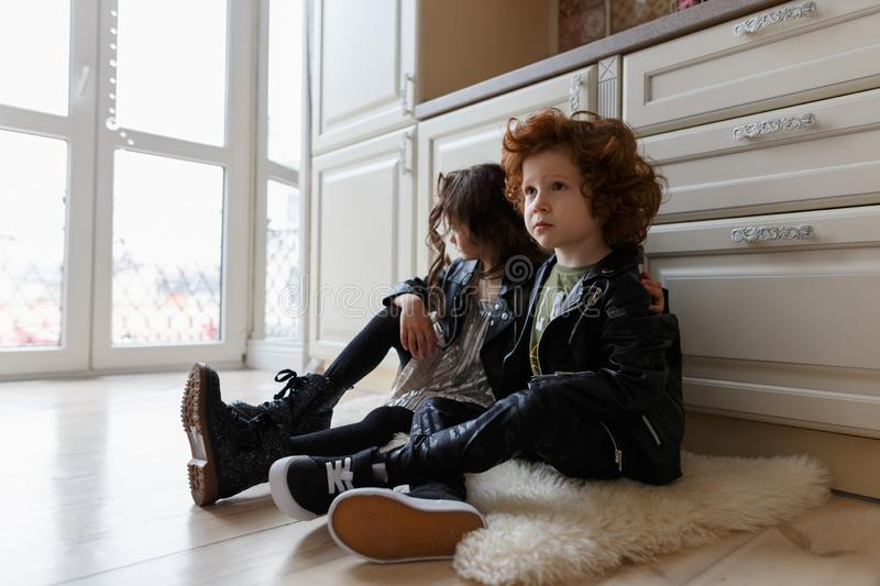 Boy and girl friends sit together on the floor royalty free stock photo