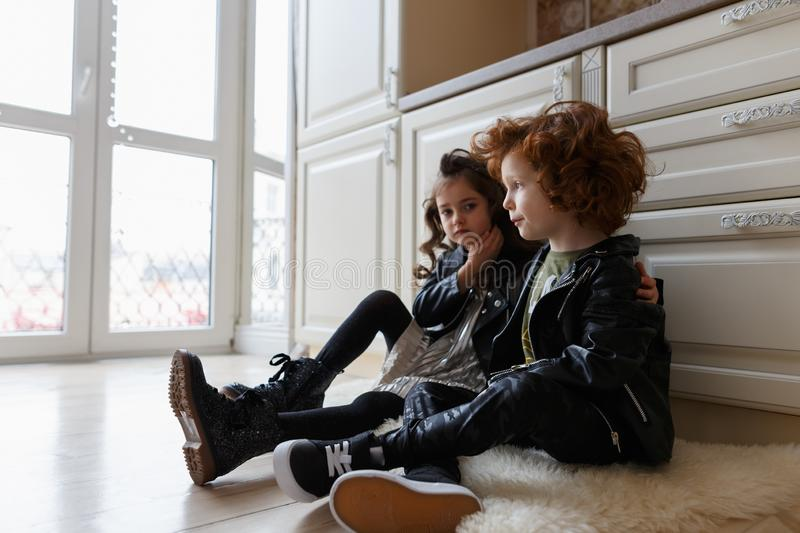 Boy and girl friends sit together on the floor stock photos