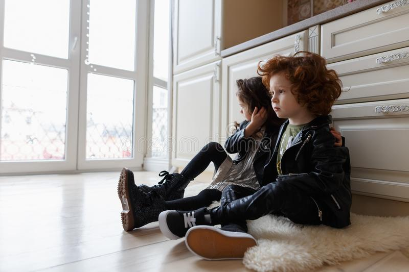 Boy and girl friends sit together on the floor stock photo