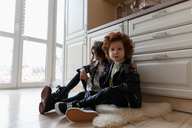 Boy and girl friends sit together on the floor stock images