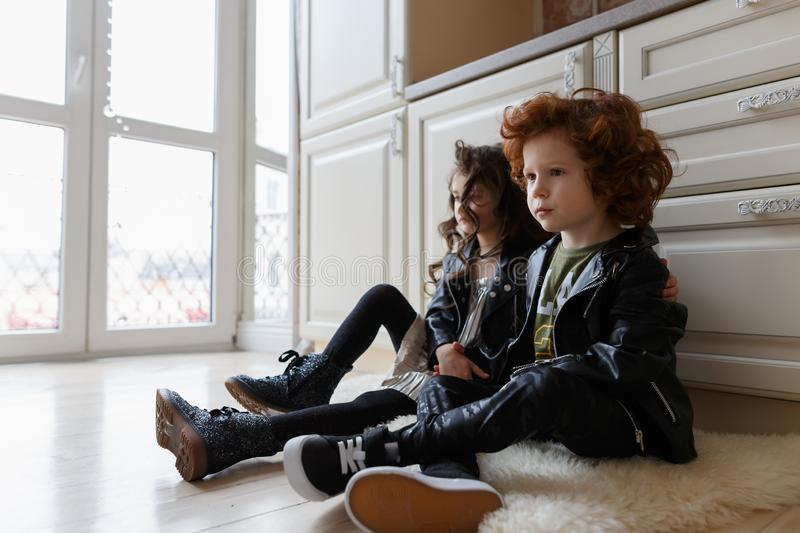 Boy and girl friends sit together on the floor royalty free stock photography