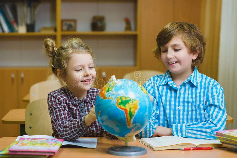 Boy and girl on the geography lesson in school classroom. Educational concept.  stock photo