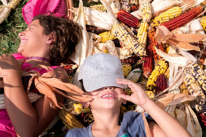 Boy and girl having fun surrounded by colorful corncobs royalty free stock photography