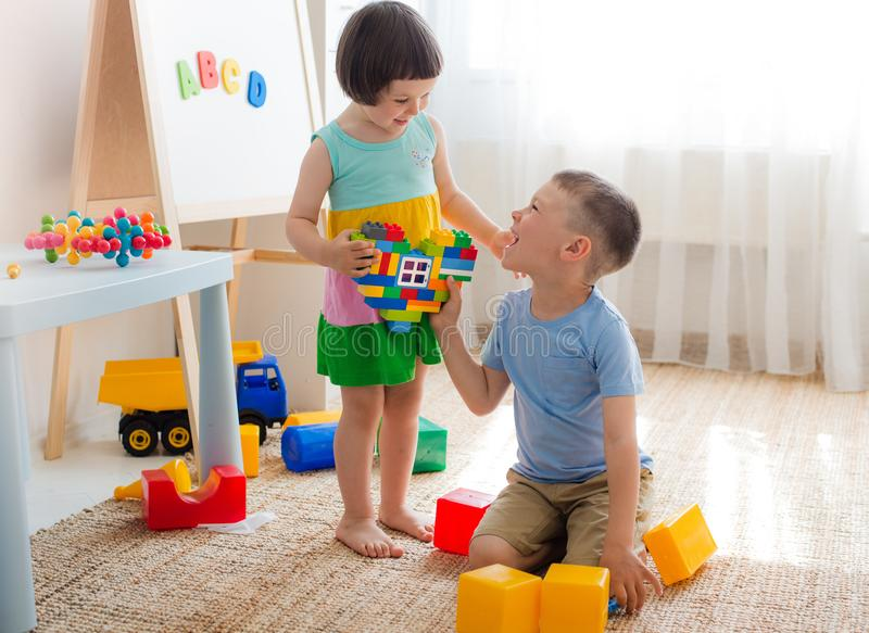 A boy and a girl are holding a heart made of plastic blocks. Brother and sister have fun playing together in the room. Preschool children and educational toys royalty free stock images