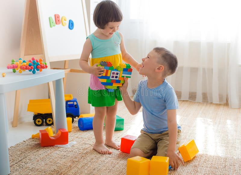 A boy and a girl are holding a heart made of plastic blocks. Brother and sister have fun playing together in the room. Preschool children and educational toys royalty free stock photos