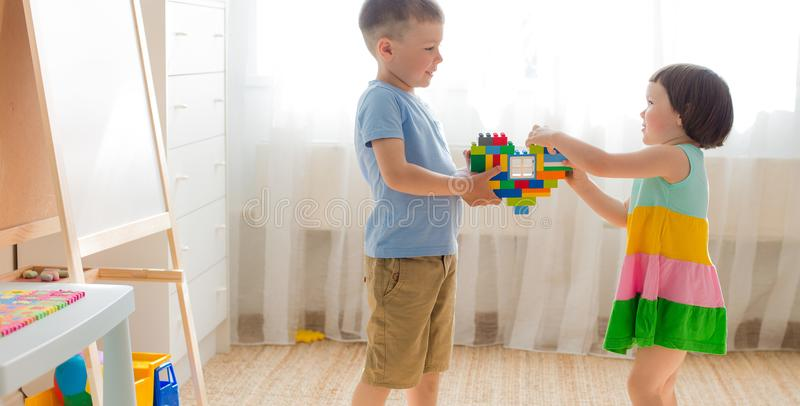 A boy and a girl are holding a heart made of plastic blocks. Brother and sister have fun playing together in the room. Preschool children and educational toys stock images