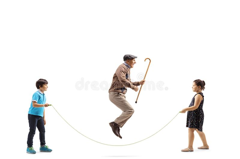Boy and girl holding a rope and a senior man with a cane jumping. Full length profile shot of a boy and girl holding a rope and a senior men with a cane jumping royalty free stock photography