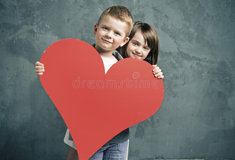Boy and girl holding a toy heart. Boy and girl holding a paper heart stock photography