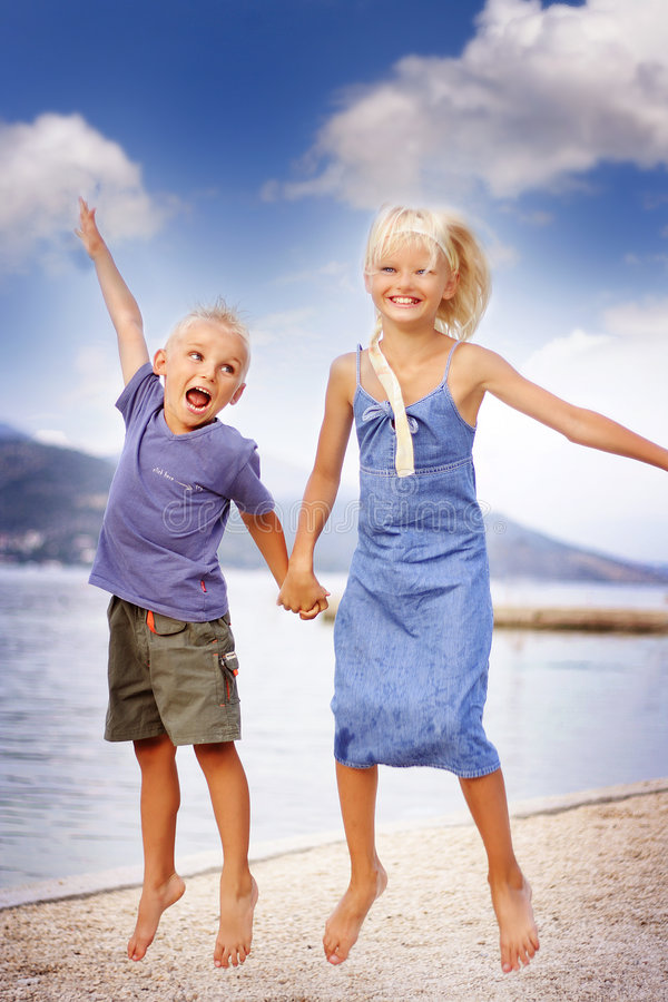 Boy and girl jumping stock photos