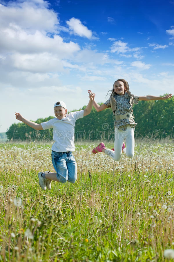 Boy and girl jumping at meadow stock image