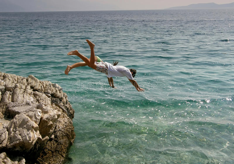 Boy and girl jumping into the sea royalty free stock image
