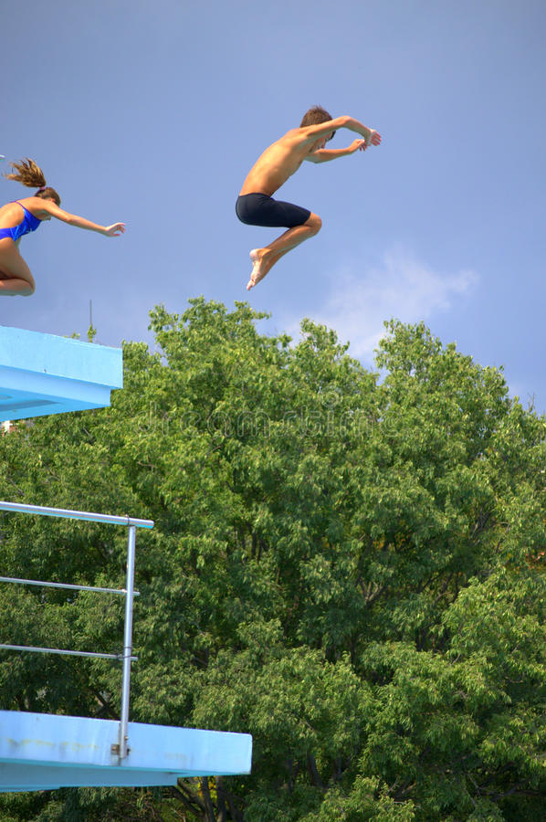 Boy and girl jumping from springboard stock image
