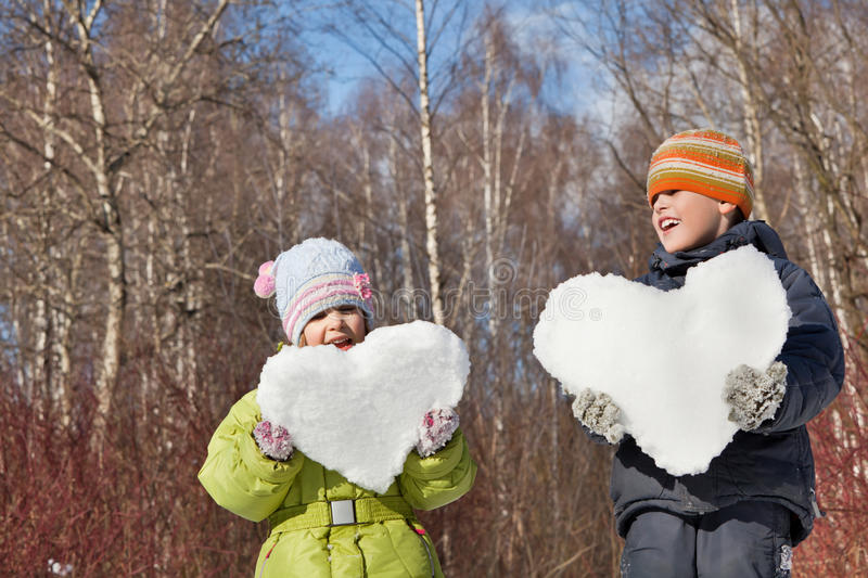 Boy and girl keeps in hands hearts from snow. Boy and little girl keeps in hands hearts from snow in winter in wood royalty free stock image