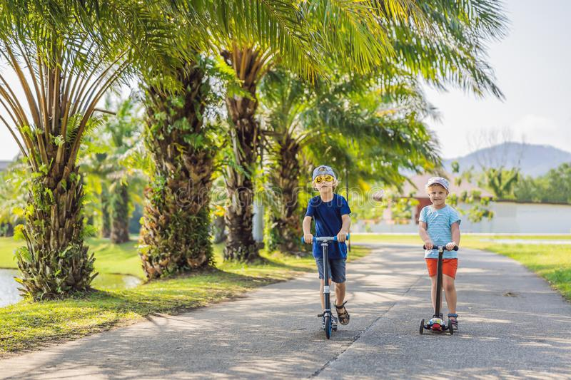 Boy and girl on kick scooters in park. Kids learn to skate roller board. Little boy skating on sunny summer day. Outdoor royalty free stock images