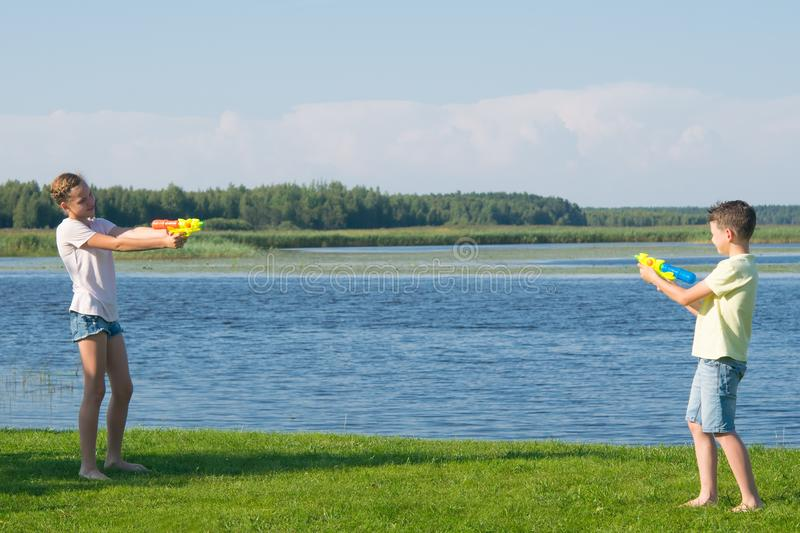 Boy and girl on the lake, on the green grass, playing water pistols, pointing them at each other royalty free stock photography
