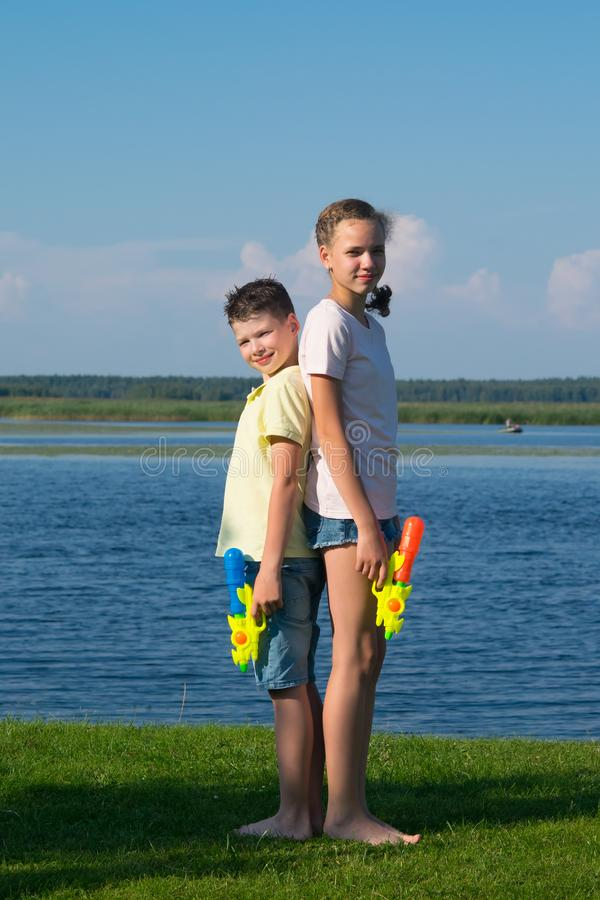 Boy and girl on the lake, holding water pistols and stand with their backs to each other, against a beautiful landscape royalty free stock photos