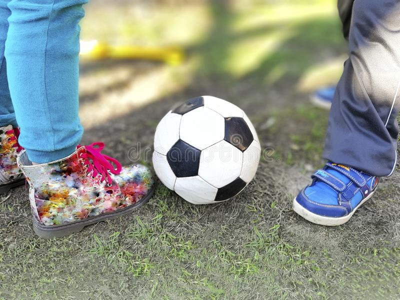 Boy and girl legs with soccer ball on spring green grass. royalty free stock photos