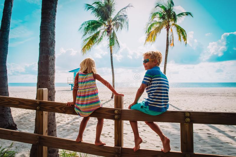 Boy and girl looking at tropical beach with palms, family on vacation in Florida. USA stock photo