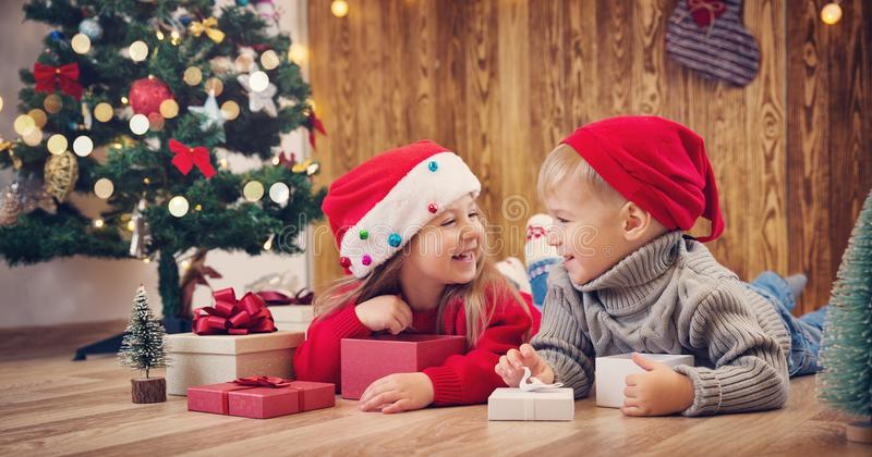 Boy and girl lying on the floor with presents near christmas tree stock image