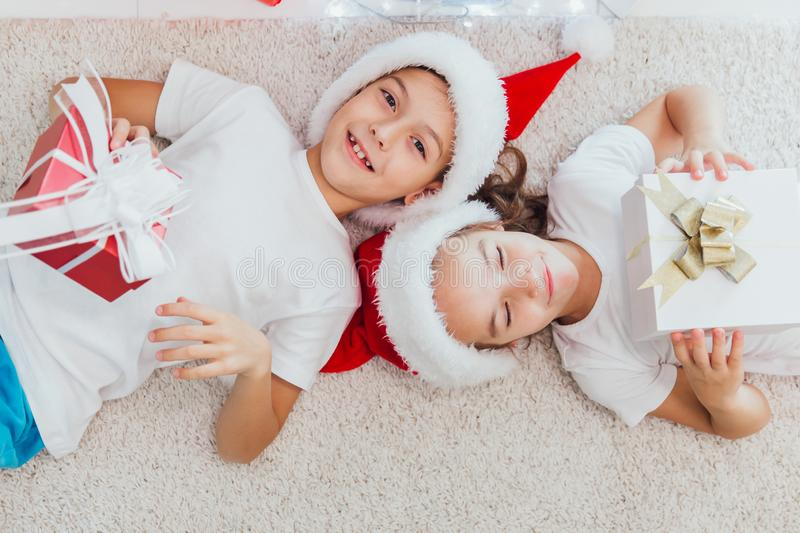 Boy and girl lying on the floor with presents near christmas tree. Children in red hats at home in winter stock image