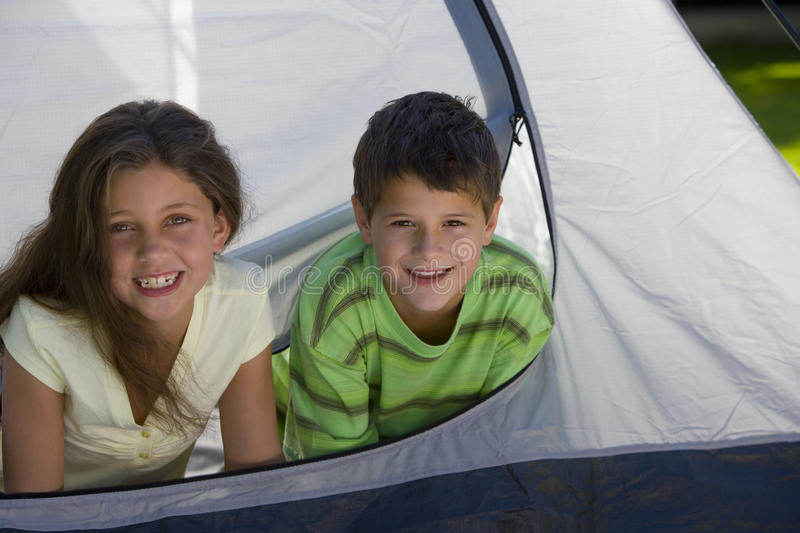 Boy and girl (8-10) lying on front inside tent, side by side, smiling, front view, portrait stock photo