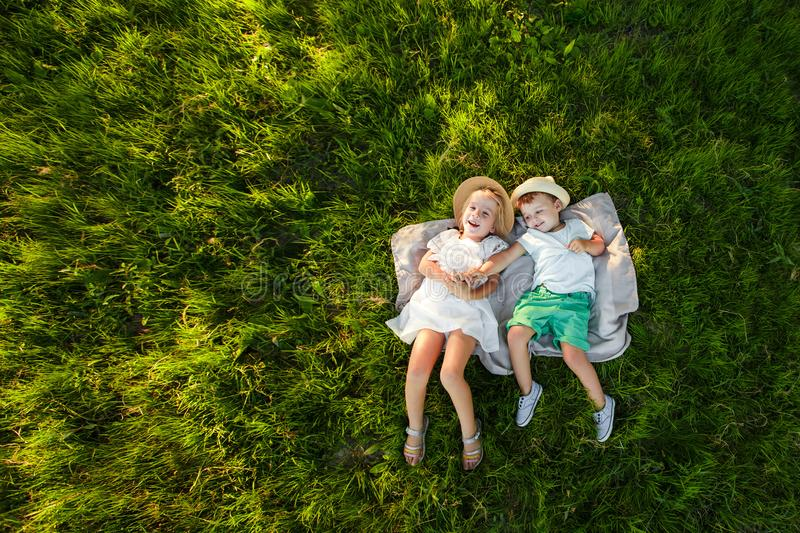A boy and a girl are lying on the green grass. Top view. Space for text. stock image
