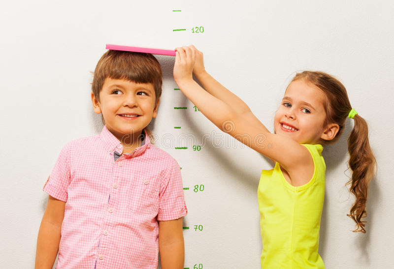 Boy and girl measure height by wall scale at home. Little 5 years old girl measure a height of boy by scale on the wall royalty free stock photos
