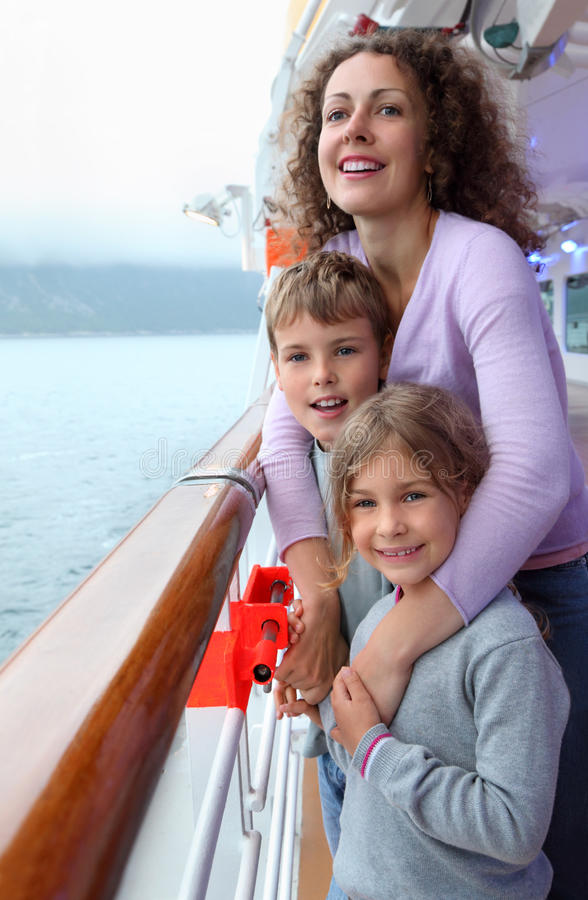 Boy and girl with mother stand on ship deck. Boy and girl with their mother stand on ship deck near coastline in Norway stock images