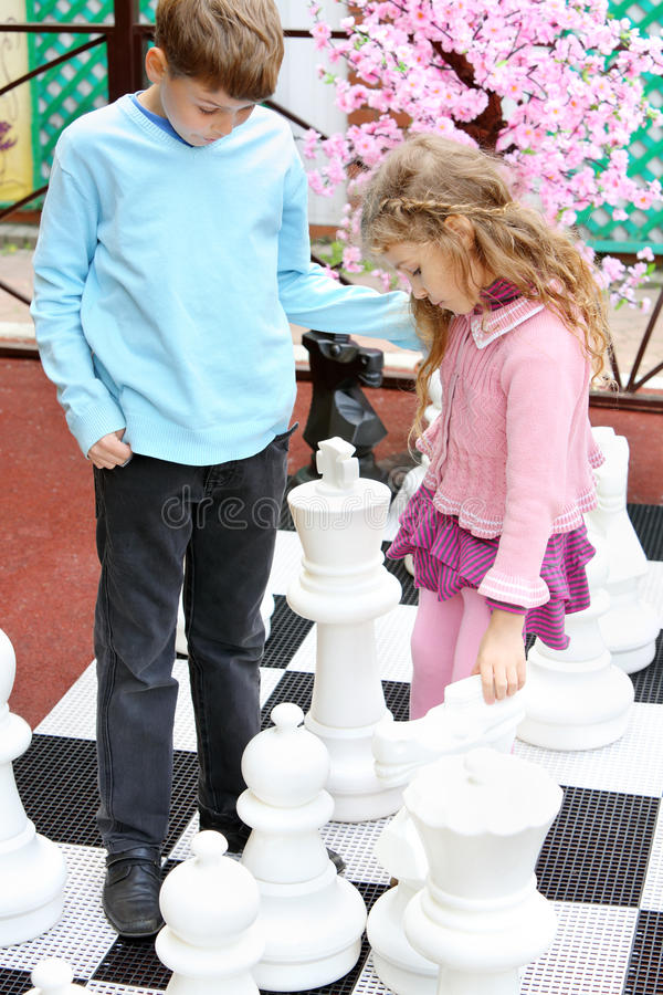 Boy and girl move big chess pieces on big chessboard. In park royalty free stock image