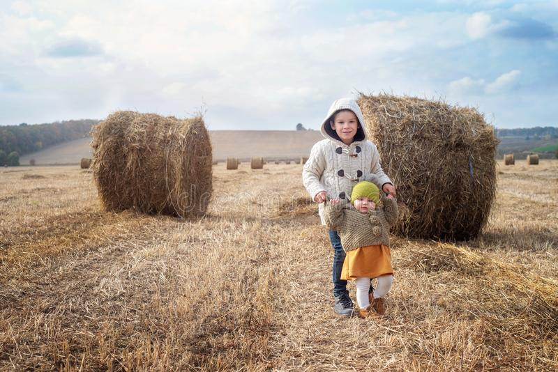 A boy and a girl near a haystack in a field at sun day on autumn next to a tractor cleans field stock photo