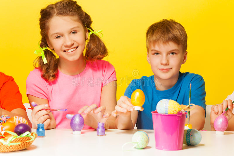 Boy and girl painting Easter eggs at the table stock image