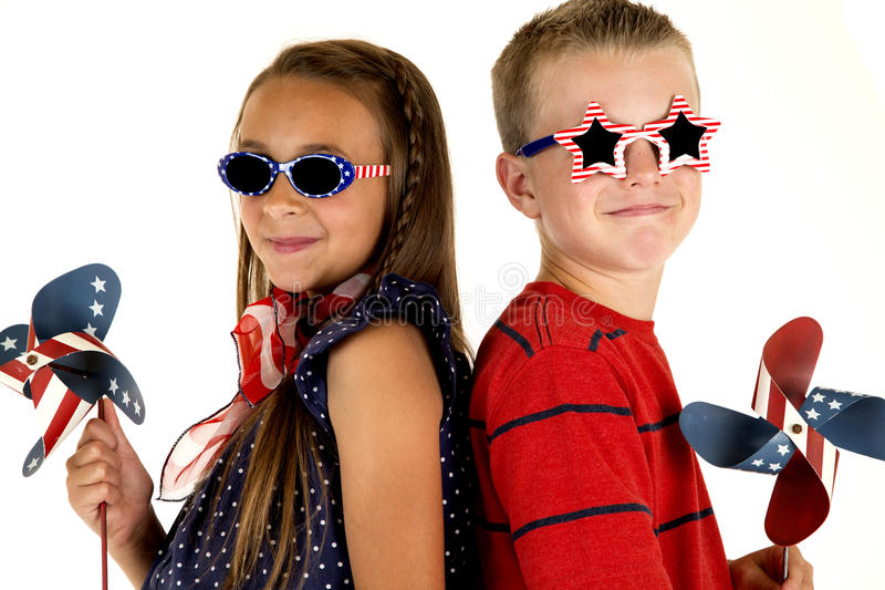 Boy and girl with patriotic windmills and glasses royalty free stock photos