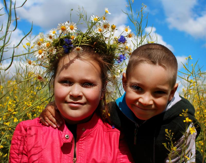 A boy and a girl play in a flower meadow stock photos