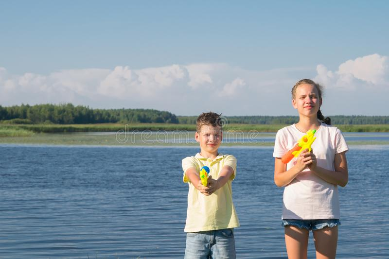 Boy and girl play water pistols against the blue lake and sky stock photography