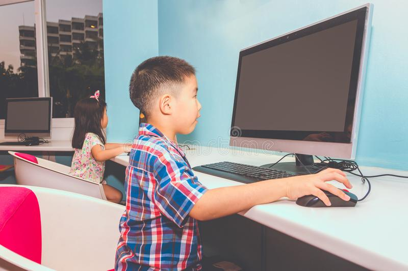 Boy and Girl playing with a computer royalty free stock image