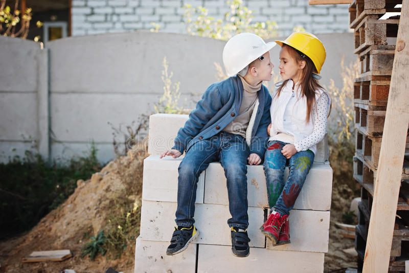 Boy and girl playing on construction site stock photography