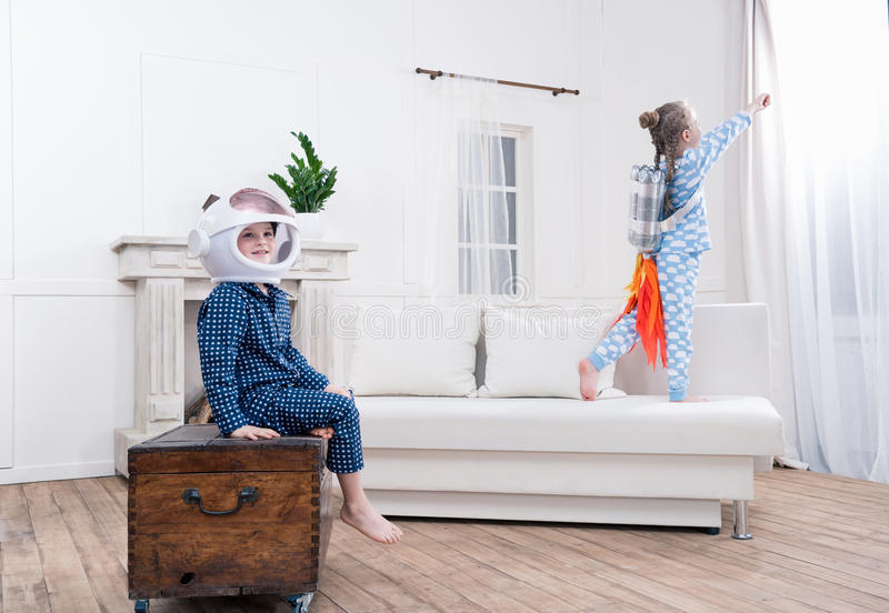 Boy and girl playing cosmonauts at home. Side view of boy and girl playing cosmonauts at home royalty free stock image