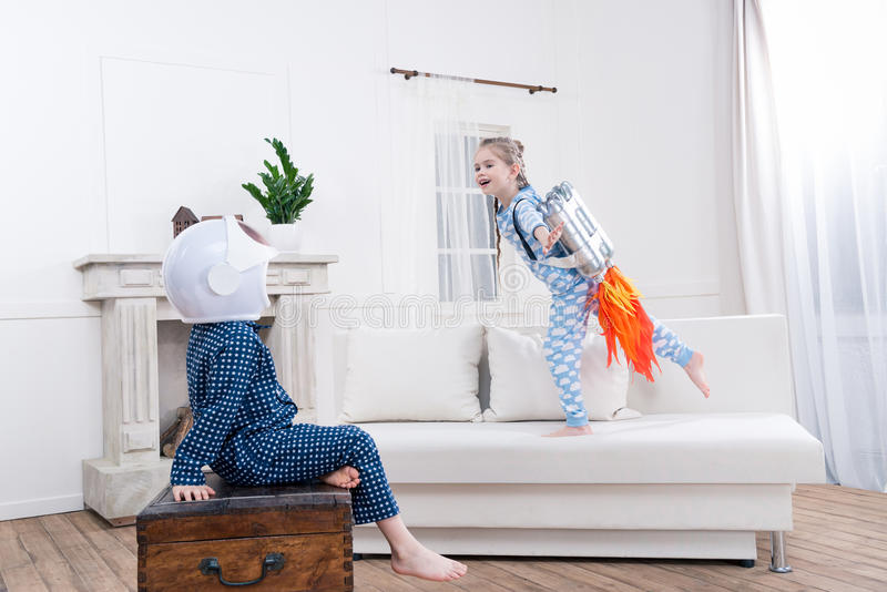 Boy and girl playing cosmonauts at home. Side view of boy and girl playing cosmonauts at home stock image