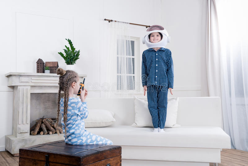 Boy and girl playing cosmonauts at home. Side view of boy and girl playing cosmonauts at home stock photography