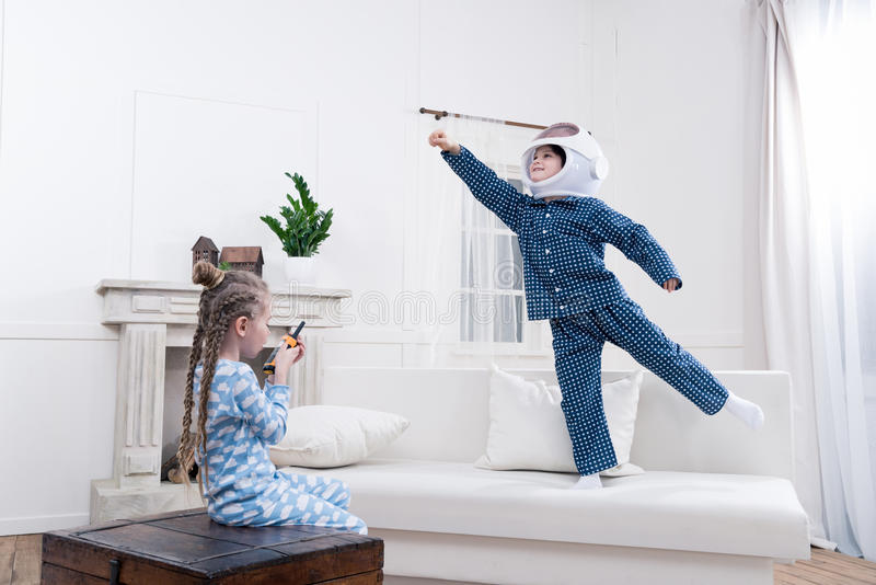 Boy and girl playing cosmonauts together. Side view of boy and girl playing cosmonauts together stock images