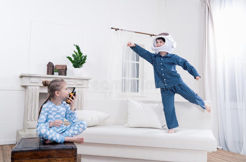 Boy and girl playing cosmonauts together. Side view of boy and girl playing cosmonauts together stock photo