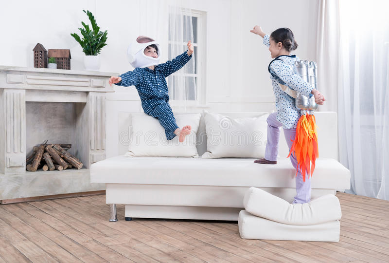 Boy and girl playing cosmonauts together. Side view of boy and girl playing cosmonauts together royalty free stock photos